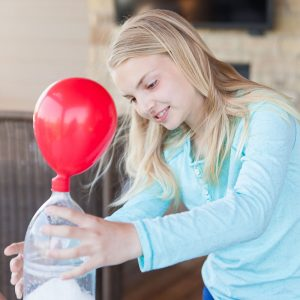 girl doing a science experiment with balloon and bottle